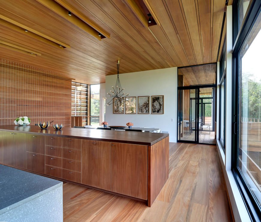 The rich hardwood flooring is complemented by minimalist paneling on the lengthy island and the ceiling, running uniformly throughout the entire home. Full height glass panels visually open the space to share the outdoors.