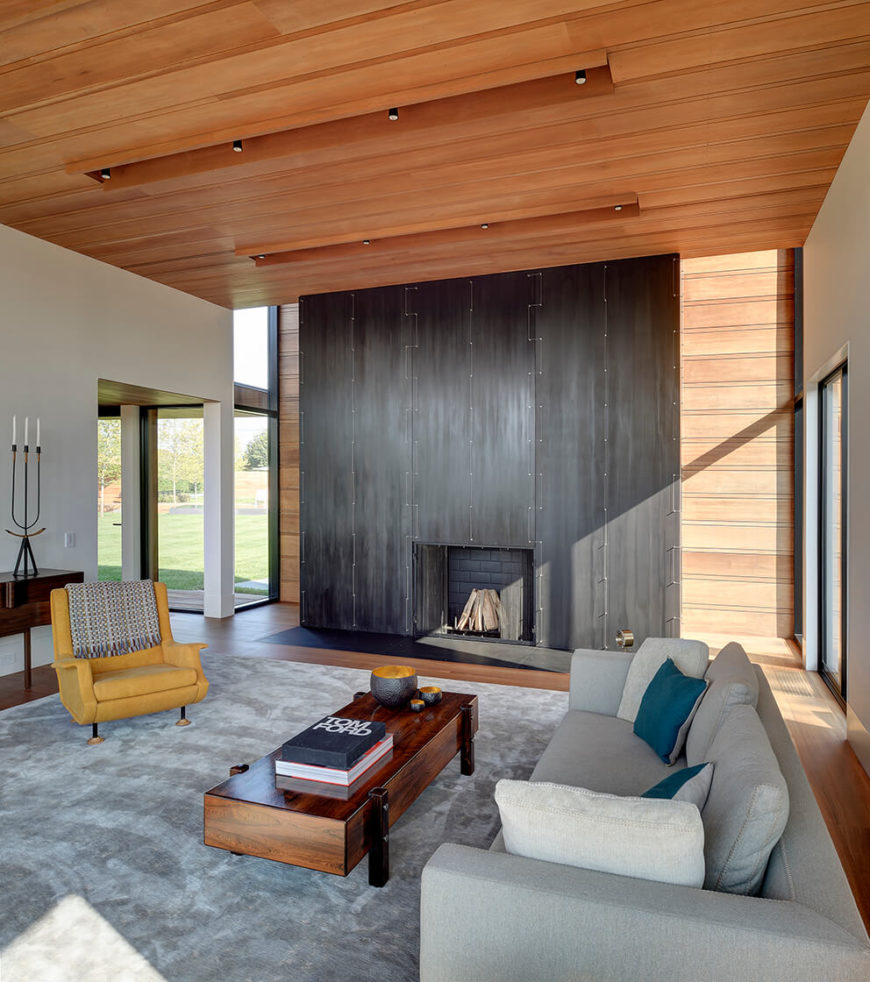 The living room centers around an immense fireplace structure in deep grey. A grey area rug holds sleek rustic coffee table and contemporary seating in grey and yellow.