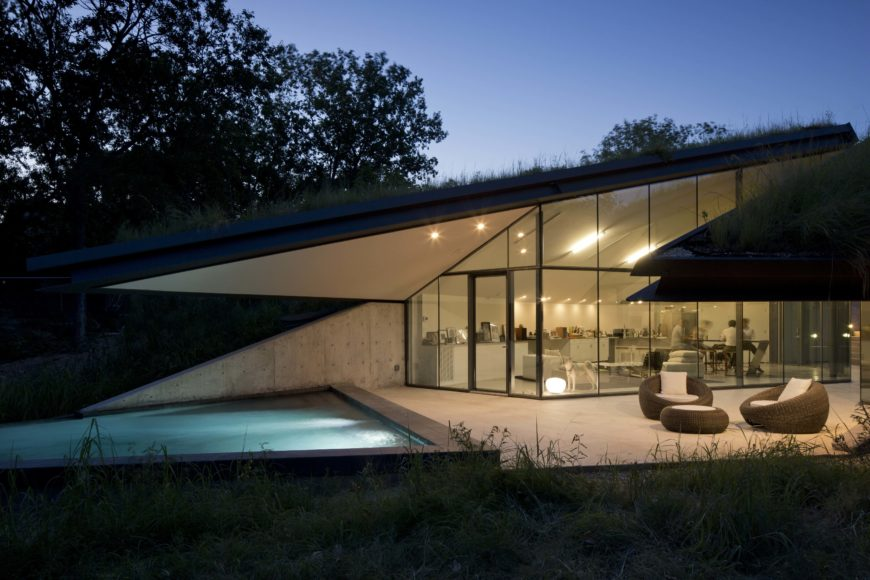 At dusk, the interior lights glow over the bookended patio space. The green roof can be seen in silhouette, growing thick over the structure.