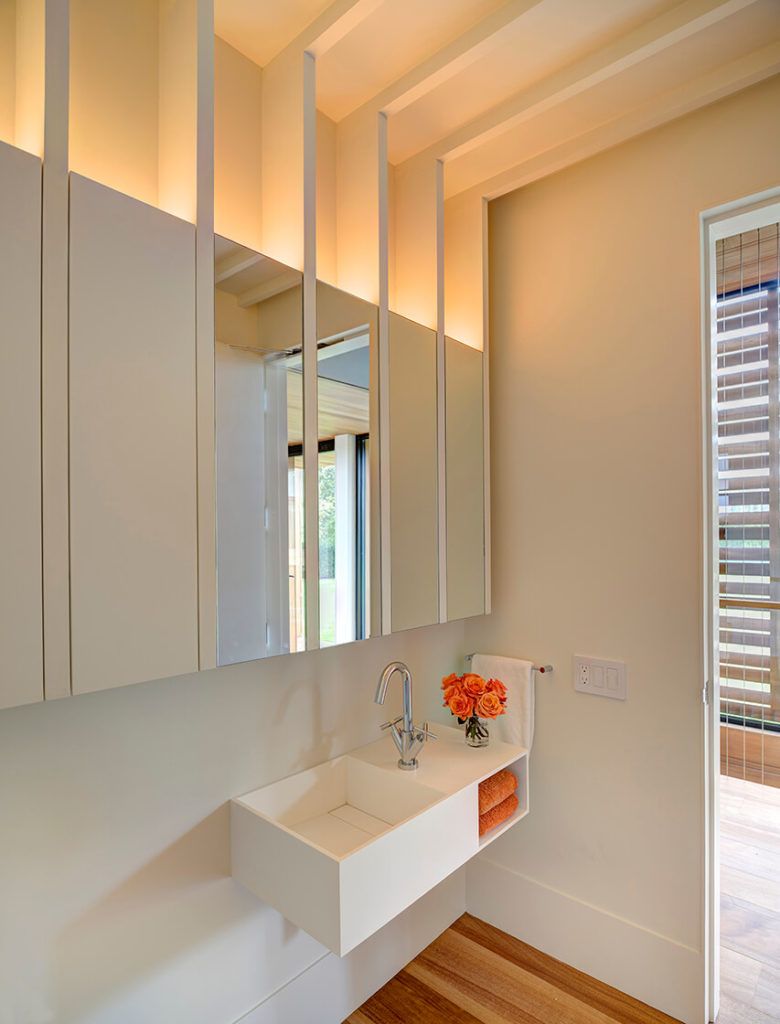 This smaller bathroom features an ultra-modern white floating vanity with cubic sink, beneath a mirror in vertical strips.