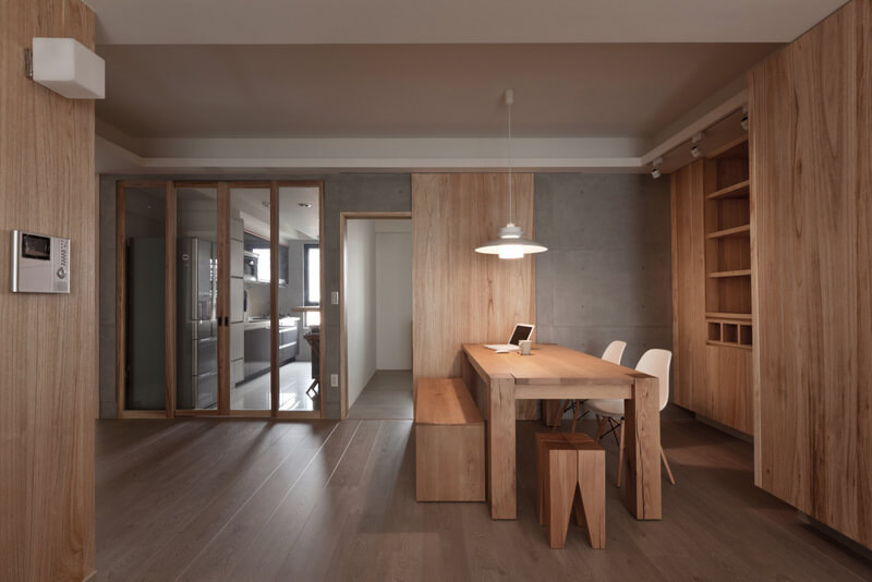 Moving closer, we see the dining room, defined by its matching wood tones on the shelving and large dining table. White chairs and single pendant lamp create a burst of brightness.