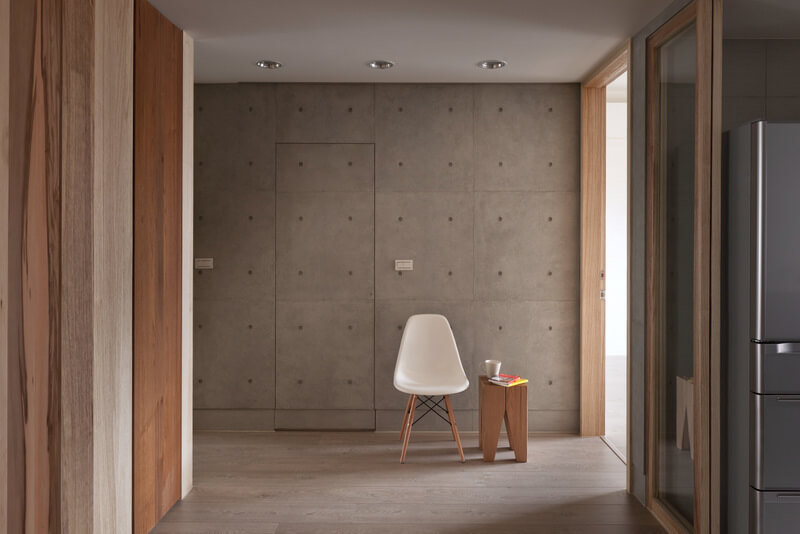 In the open hall space, concrete walls are exposed for a unique aesthetic, contrasting with the bright hues of wood details and white ceilings.