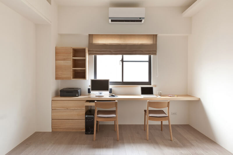 The home features an office with a built-in light wood desk and matching shelving, in contrast with all-white surroundings.