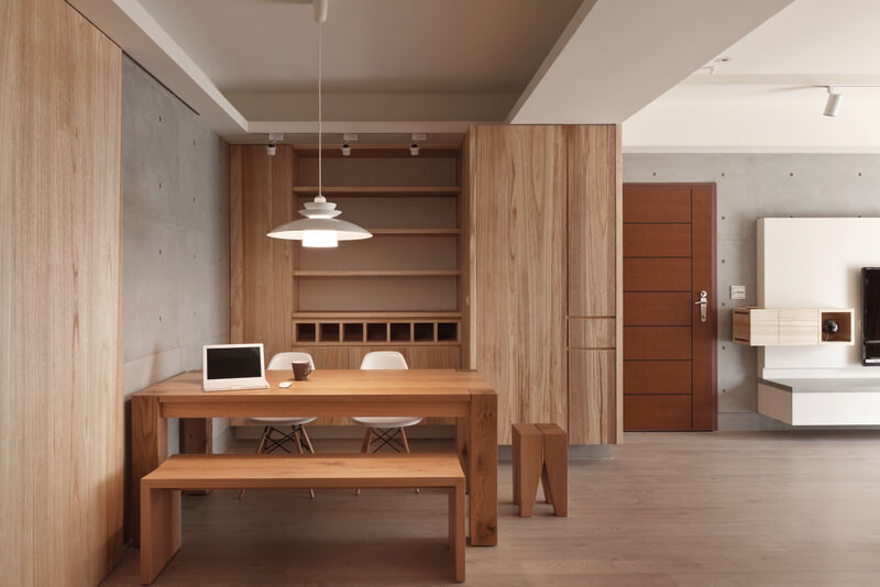 The array of shelving and storage built into the wall stands next to the entry door, defining the dining area from the larger living room. The table shares seating with a pair of white chairs, plus bench and cubic stool in matching wood tones.