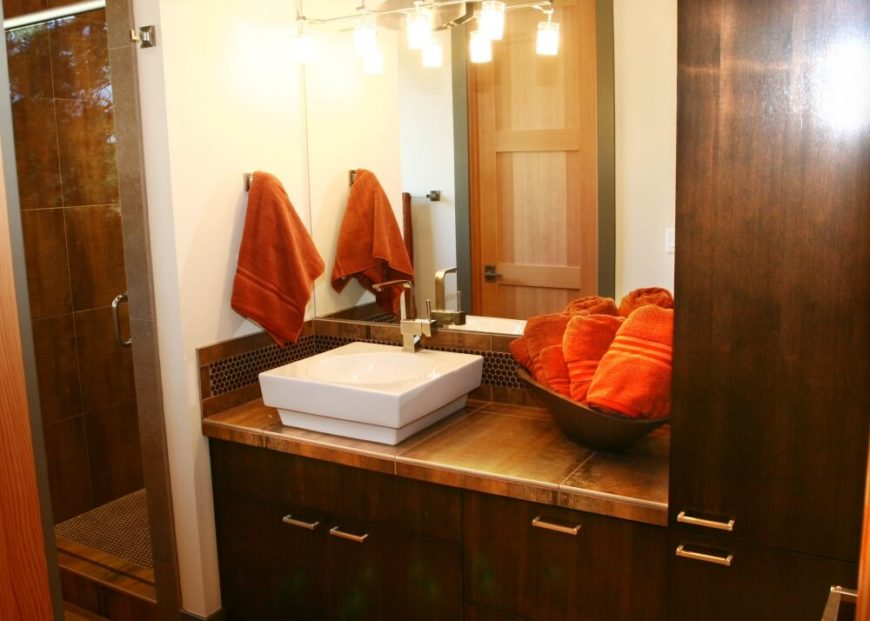 The primary bedroom's suite continues the dark wood and bold orange-red of the bedding, but adds bronzed tile to the mix. A white square vessel sink pops against the countertops.