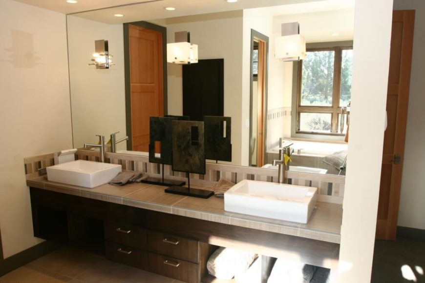 A spacious primary bedroom with his-and-hers vessel sinks and towel storage beneath the right sink.