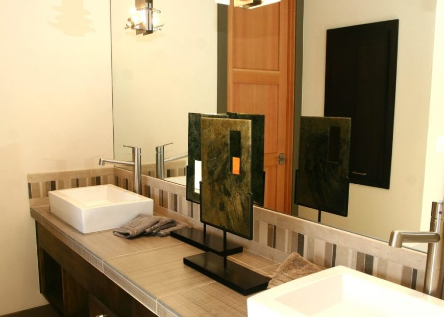 A close-up on the sinks, highlighting the texture of the tile countertops and the two modern sculptures between the sinks.