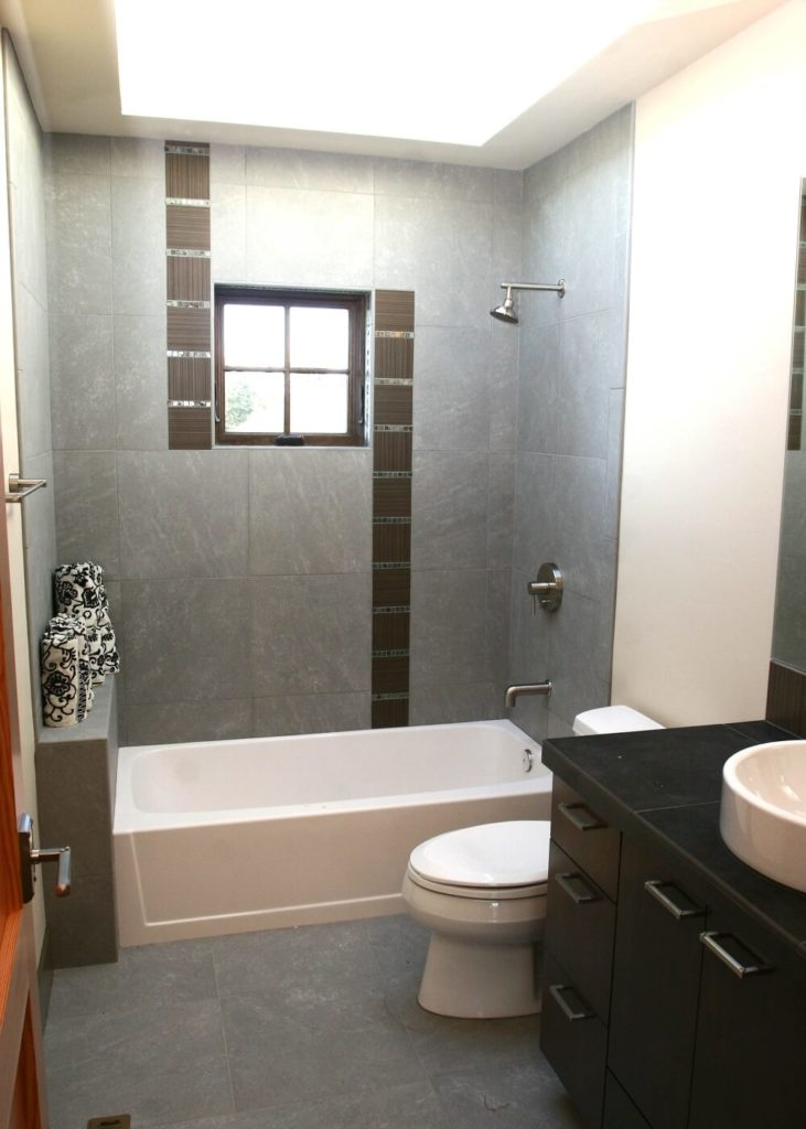 The upstairs bathroom is in light gray tile with rich dark wood and a white vessel sink. The tile used for the backsplash also appears as a singular stripe in the midst of the gray tile around the bathtub.