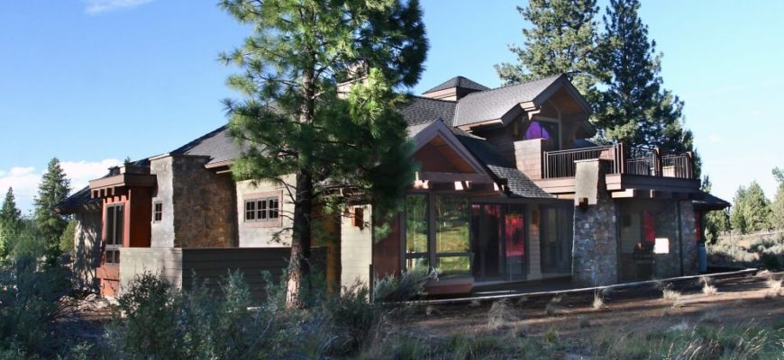 A final look at the exterior of the home from the left side behind some of the landscaping, showing the deck above the grand stone and wood entryway.