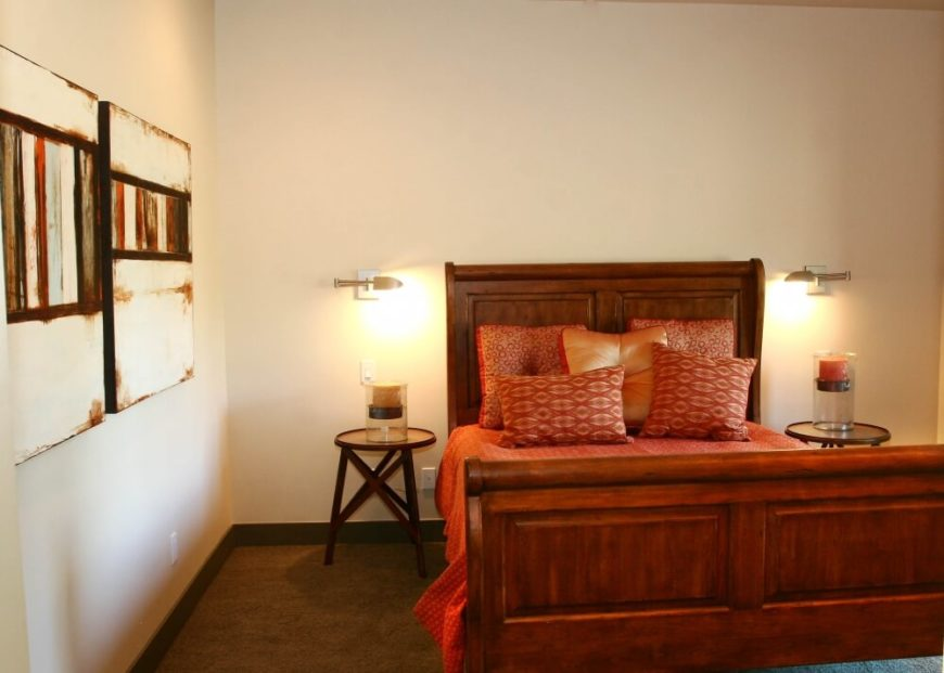 One of the two primary bedrooms on the main floor in ivory walls and light brown carpeting. The large wood bed frame is matched with smaller nightstands, each with a large pillar candle in a glass holder.