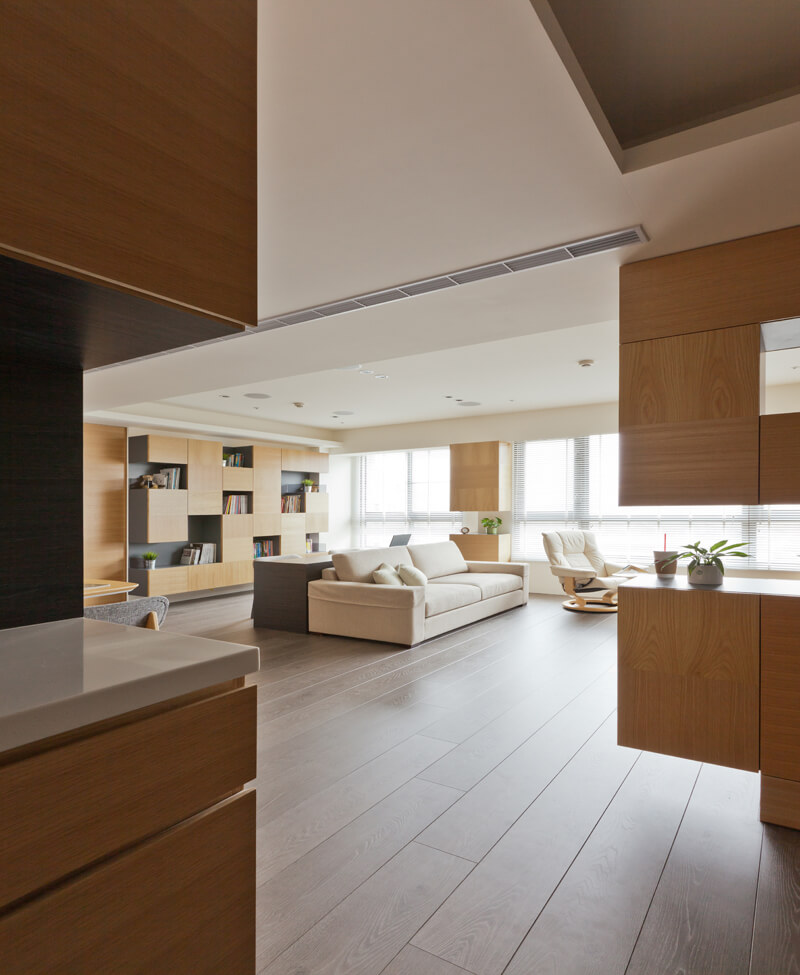 Pulling back near the entrance, we see the expanse of rich hardwood flooring spread out beneath the open design home.