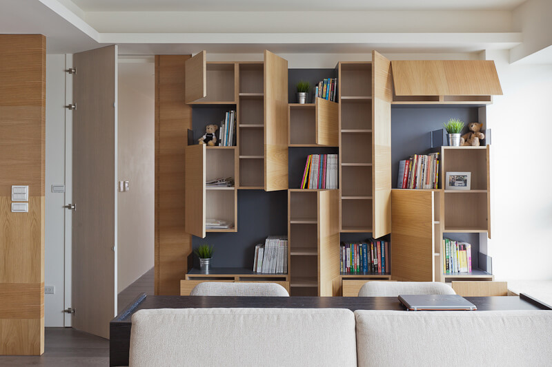 The cubic shelving opens in surprising ways, with panels both vertically and horizontally hinged, revealing interior storage.