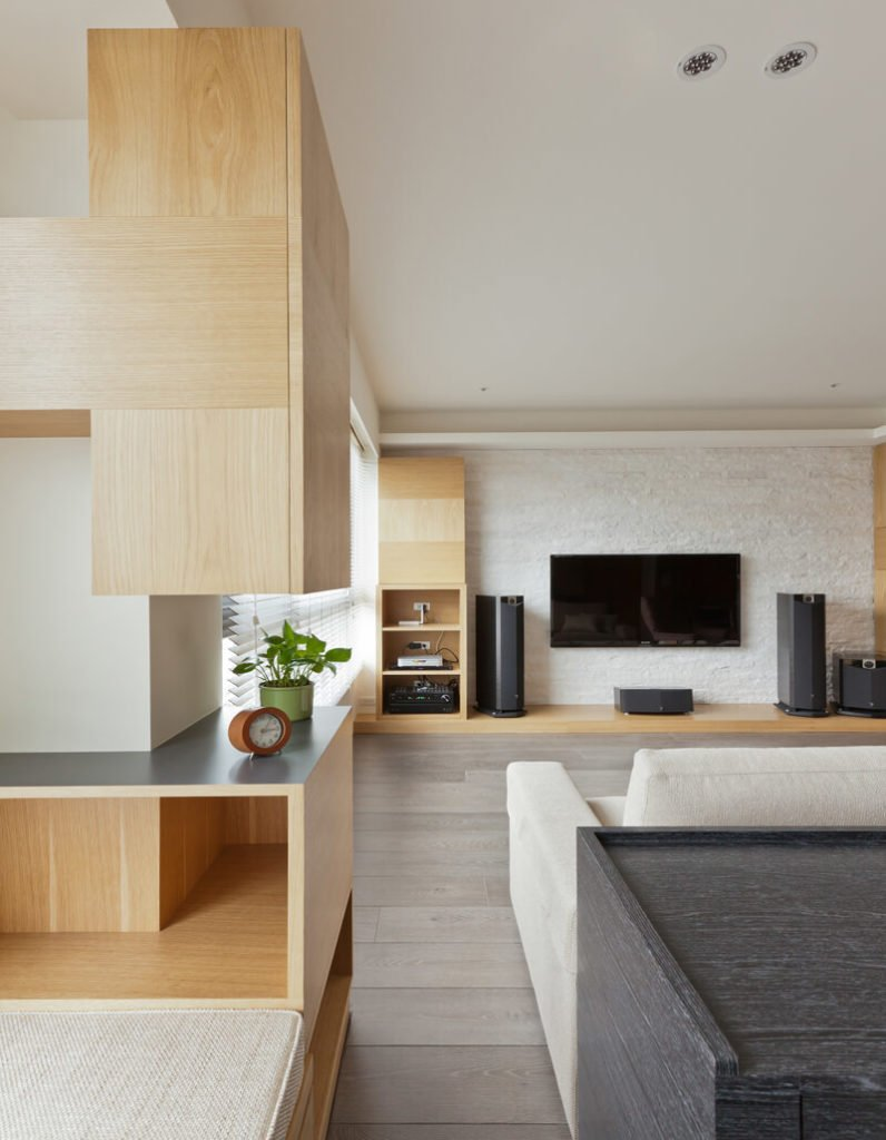 The dark toned desk works in contrast with the light cushioning, warm wood tones, and white walls surrounding.
