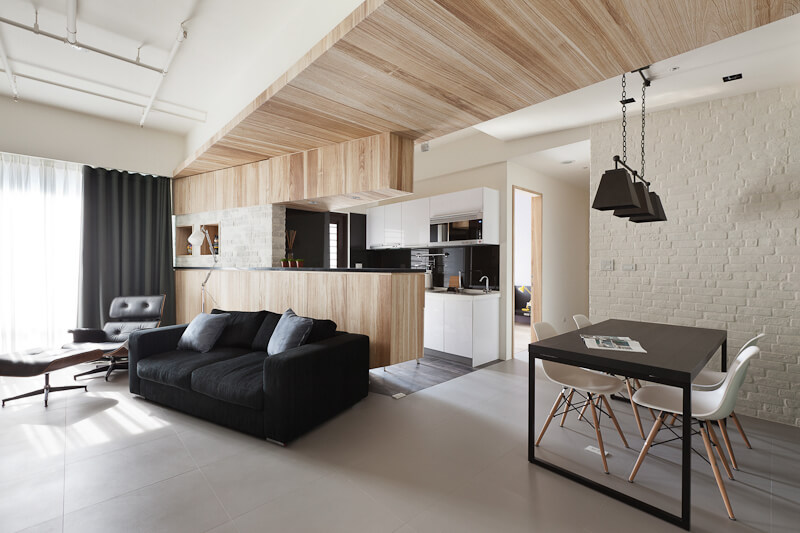 The central open plan space includes a living room and this kitchen and dining area. Black hued furniture contrasts with the white walls and light toned wood paneling.