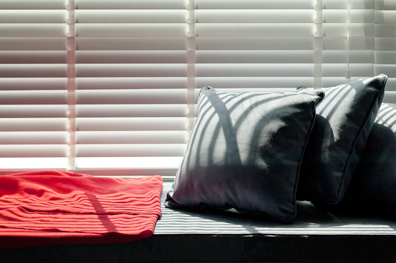 A small window seat relaxing space sits below the large full-height window in the bedroom.