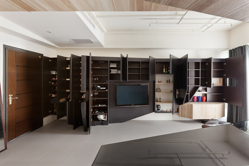 Turning toward the living room, we see how the wall-length expanse of angular cabinetry looks when fully opened, revealing an abundance of storage options.