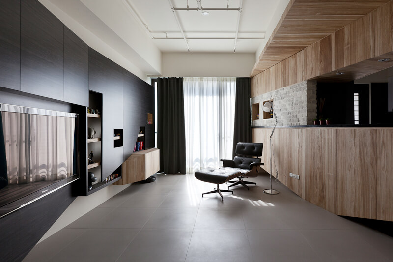 Large format tile flooring spread out beneath the entire open space. Minimalist dark wood cabinetry at left provides an angled, sleek structure in contrast with the lighter wood of the kitchen, and sunlight via the full height window at back.