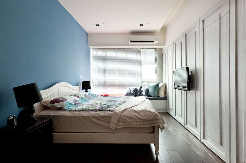 The primary bedroom features dark hardwood flooring, wall-length panels in white, and a bold blue wall behind the wood frame bed. Full height window grants natural light throughout.