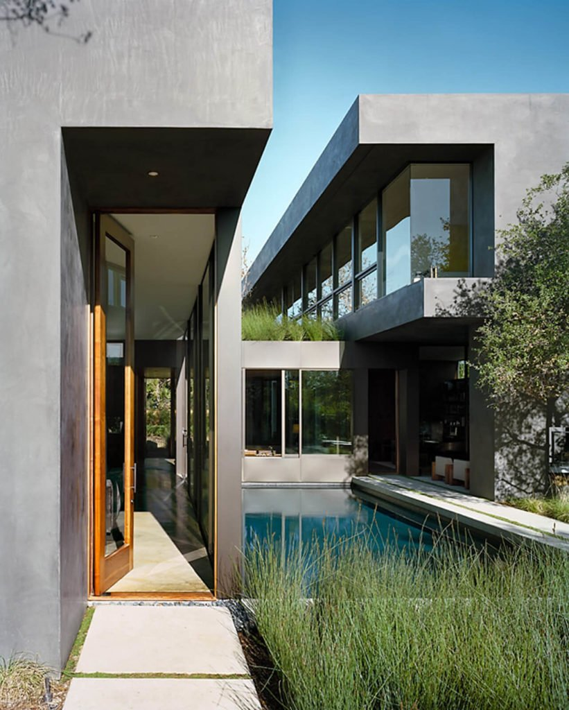 Here we clearly see the sunken kitchen connecting the two wings of the house, overlooking the pool. Greenery surrounds the space, appearing even on the roof of the kitchen.