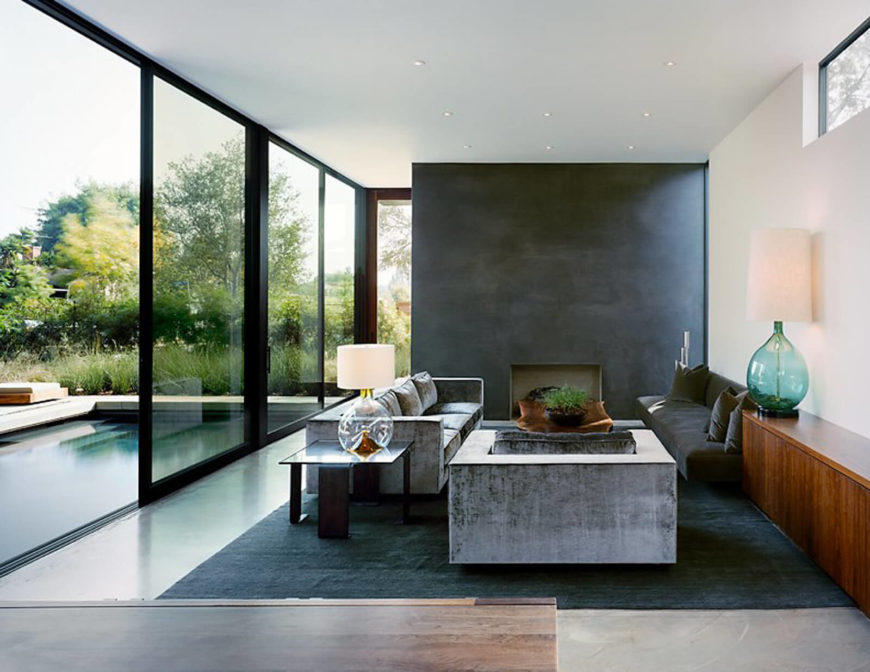 Viewed in the opposite direction, we see the living room furniture, a set of neutral contemporary sofas and seating on a dark area rug. Monolithic charcoal toned fireplace fills the wall space.