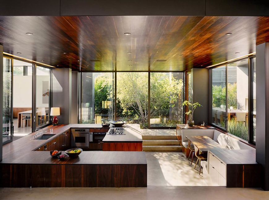 The raised level within the kitchen overlooks the entire space, vertically divided by the countertops and shelving bookending the breakfast nook. The ceiling mirrors the rich wood tones.