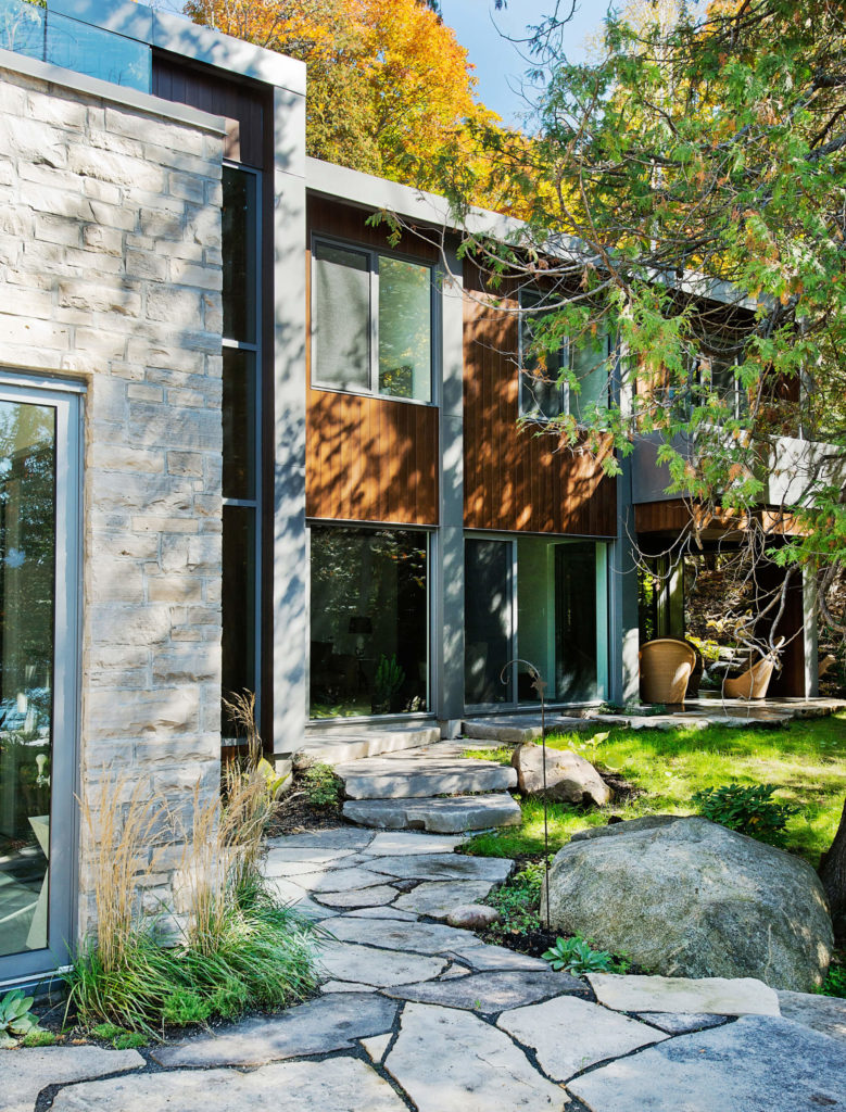 A broken stone path surrounds the property, below the expanses of full height glazing. An open, sheltered patio can be seen at right.