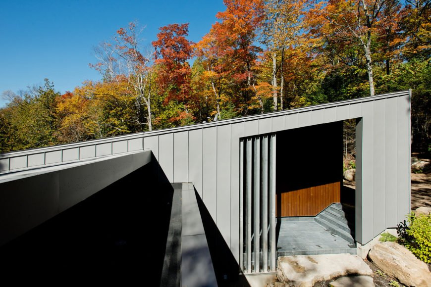 To the right, we see the sheltered entryway, where the roof slope reaches its peak. Visitors are ushered inward past a series of boulders, into a semi-indoor space.
