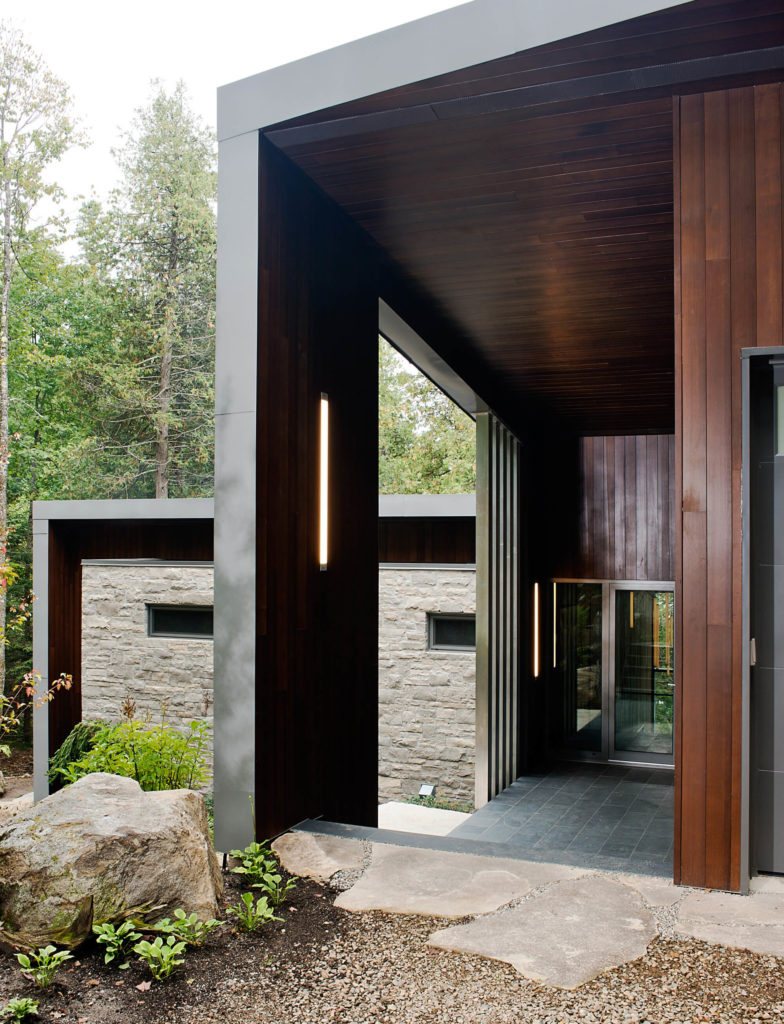 The dark tiles contrast with rich wood paneling, before reaching the metal framed glass doors.