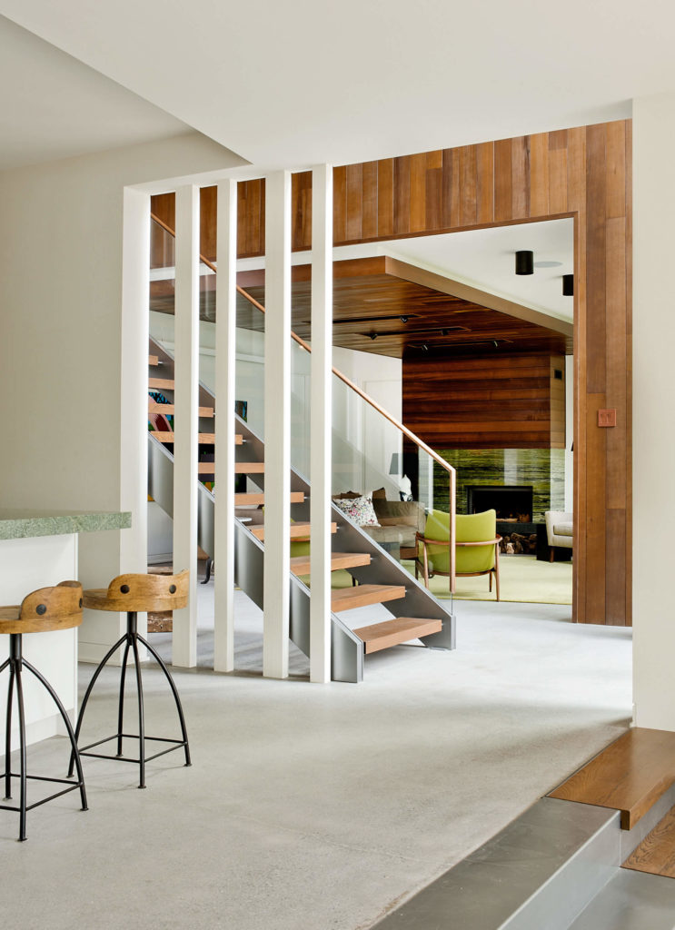 Moving past the stairs into the kitchen area, we see the complex layers of hardwood, metal, stone, and white walls interacting in this central area.