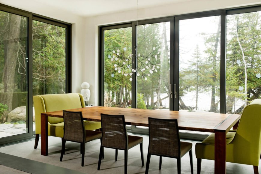 Turning around, we see the glass wrapped dining room, which opens to the outdoors via sliding panels all around. The large natural wood table is flanked by colorful seating, with views over the forest and lake beyond.