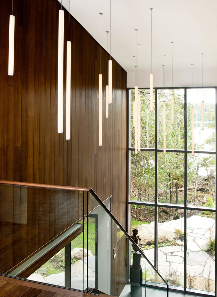 Over the grand, two story foyer, we see a series of tubular pendant lights, forming a constellation over the large space.