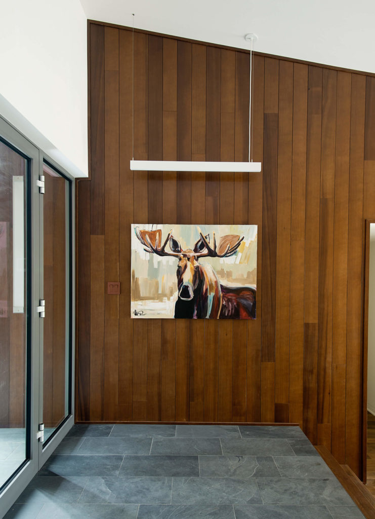 Arriving back at the main entrance, we see the rich wood wall paneling meeting the sloped ceiling. Metal framed glass doors allow entry.