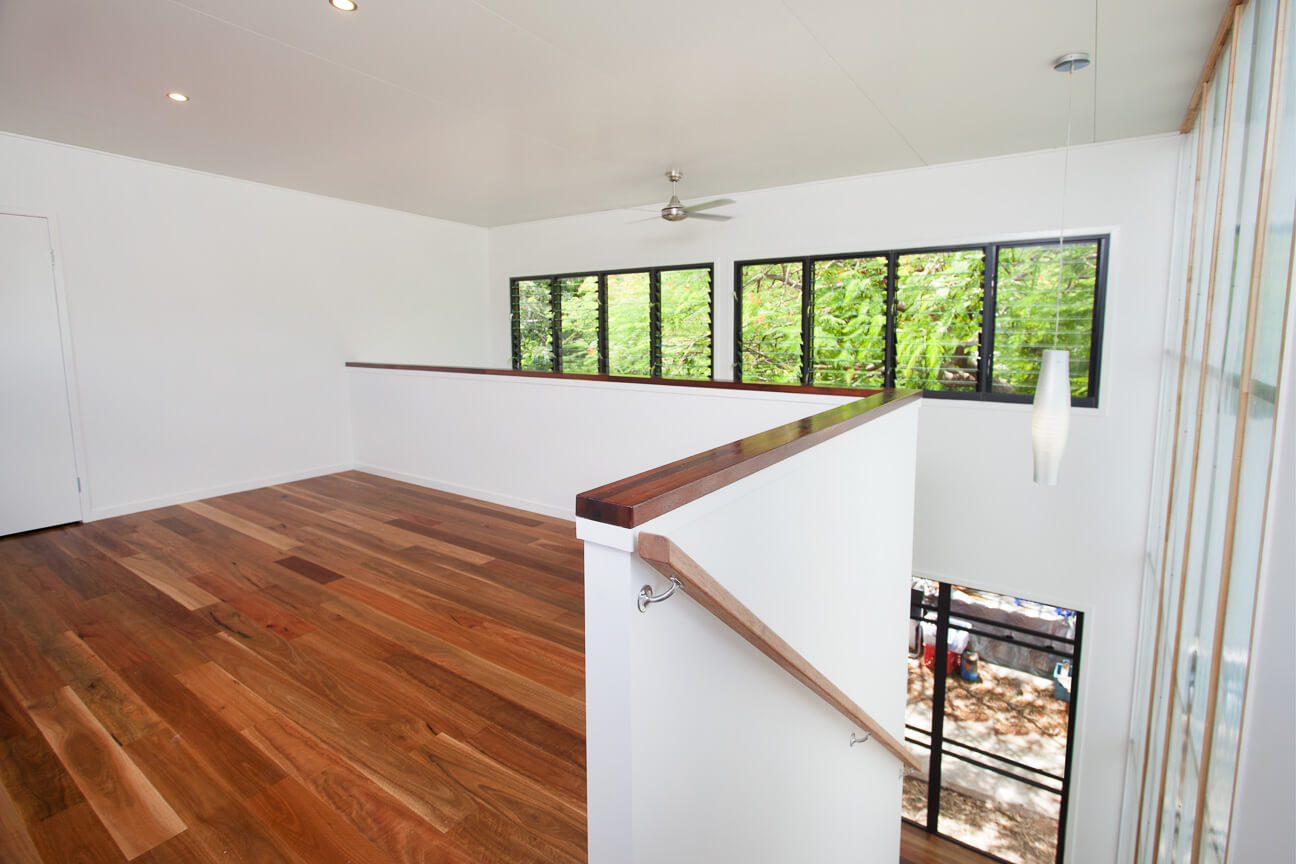 The upper level overlooks the first floor and surrounding exterior, via an expanse of windows beyond the two story void. Rich hardwood flooring contrasts elegantly with the white walls.