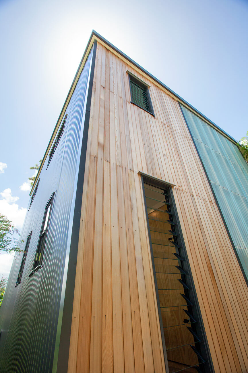 Here we see the cedar panels surrounding two sets of louvered windows, next to the transparent paneling.