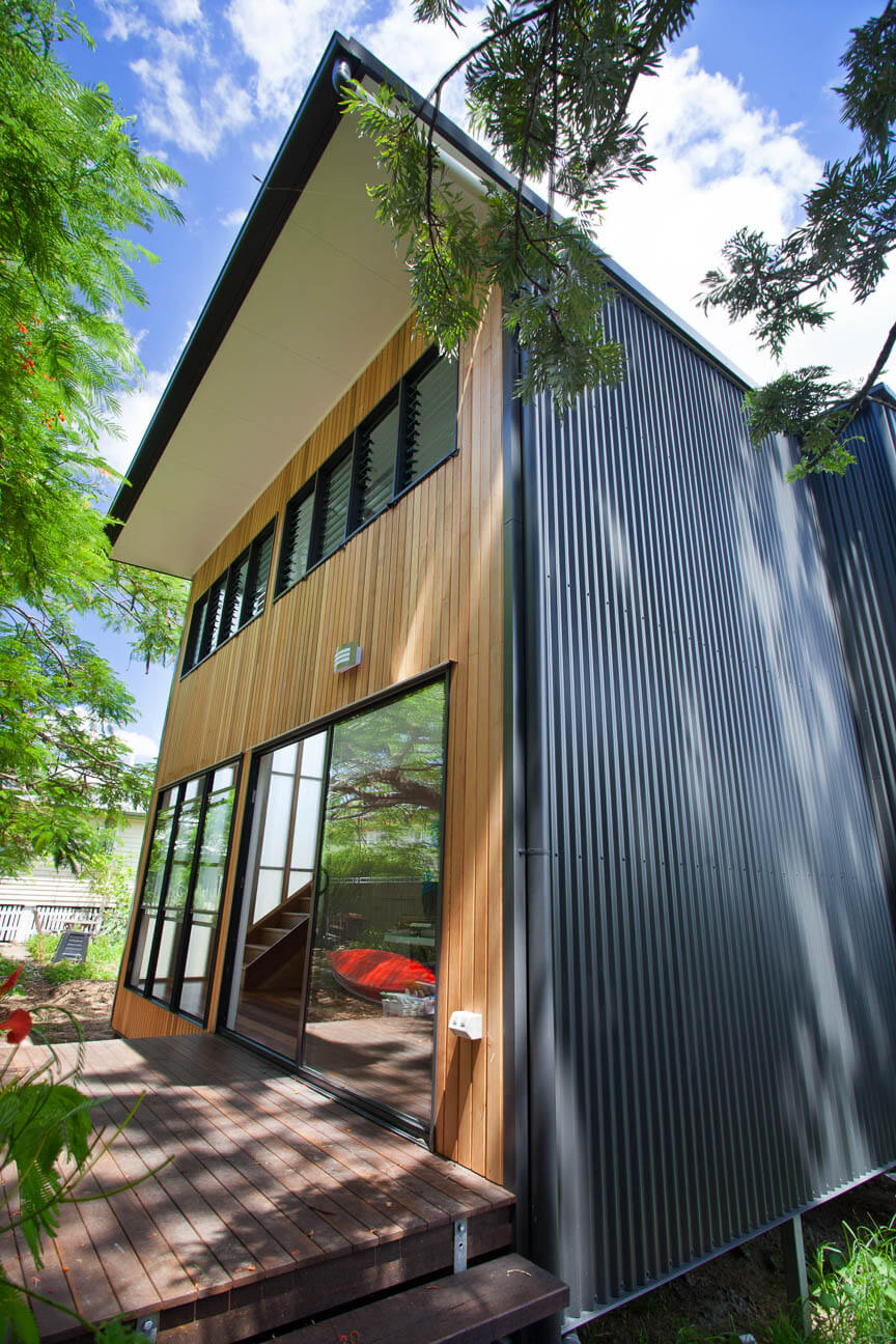 The entryway holds a large sliding door and set of full-height windows over a dark wood deck. The immense glass and transparent panels allow sunlight throughout the interior.
