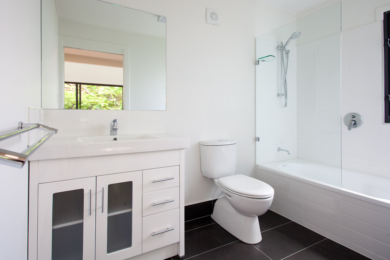 The all-white bathroom contrasts over dark large format tile flooring, with a glass enclosure shower and vanity with smoked-glass cupboards.