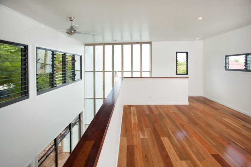 The upper level windows are slightly smaller, yet also louvered for airflow. A low wall wraps the open design space.
