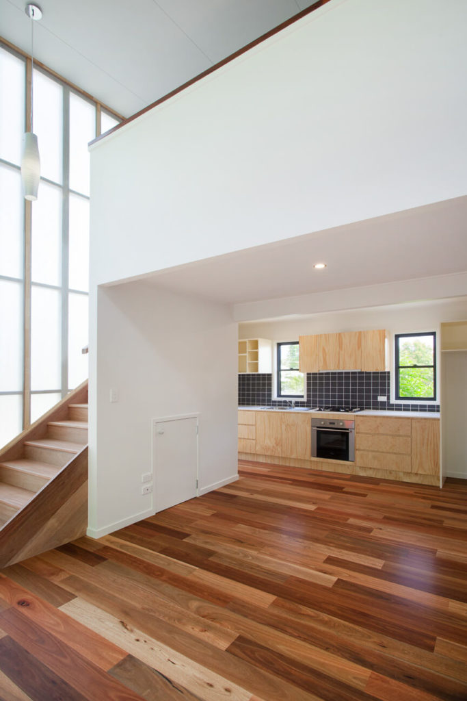 The kitchen is entered blow the overhanging second floor, an open sweep of space that leads to light natural wood cabinetry, tile backsplash, and a set of smaller rear windows.