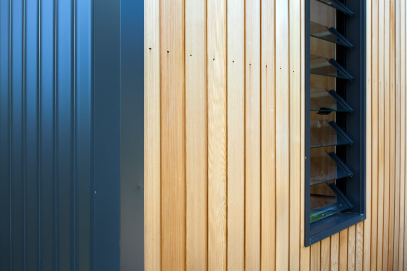 Here's a close view of the exterior, where the cedar panels meet the custom metal roofing panels.