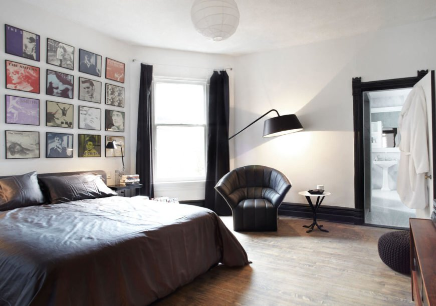 The primary bedroom mixes dark hued bedding, drapes, and armchair with light surroundings. A wall-size array of album covers by The Smiths adds a personalized, artistic touch.