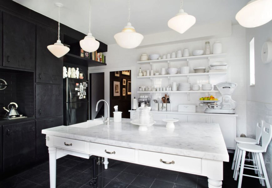 The kitchen stands in stark contrast between white walls, shelving, and marble topped island, and black tile flooring and floor to ceiling cabinetry.