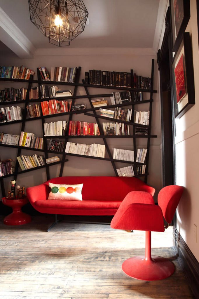 """This room features a unique """"haphazard"""" modernist bookshelf, with angular black lines echoed in the lighting framework. Bright red furniture contrasts with sedate surroundings."""