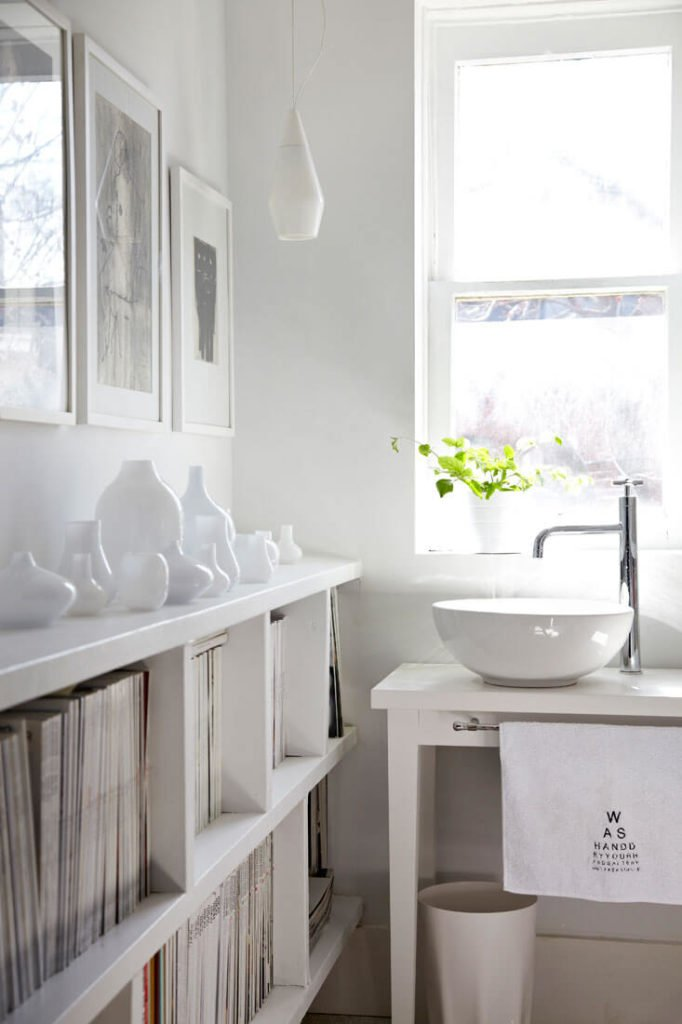 The bathroom features a mixture of traditional and modern elements, including a table-style vanity with curved vessel sink. White shelving holds a set of white glass vessels at left.
