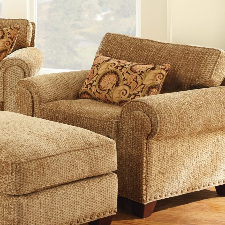 This hay-colored armchair stands in thick fabric upholstery, with a traditional roll-arm design and extra-thick padded cushioning on the seat and back.