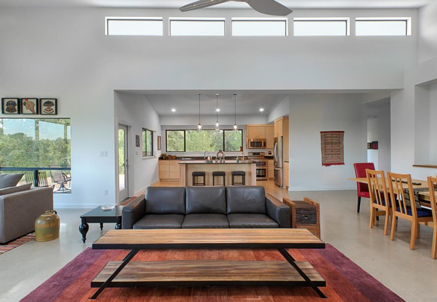 The large open space in the social half of the home orbits around a living room furniture setup, with black leather sofa and two-tiered natural wood table at the center. Natural wood and black elements repeat throughout the entire interior.