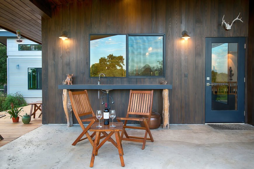Moving outdoors, we see a minimalist home bar on the patio, with a found-wood supported countertop and sink behind the folding chairs and natural wood table. Dark cedar covers the exterior here, lending a rich tone.