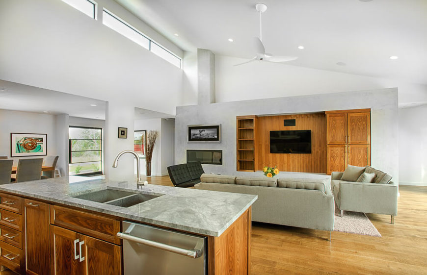 The open-plan design creates an immense central open space, with living, dining, and kitchen areas centered beneath a two story angled ceiling. The marble topped island overlooks a set of contemporary sofas and large entertainment wall featuring shelving and built-in fireplace.