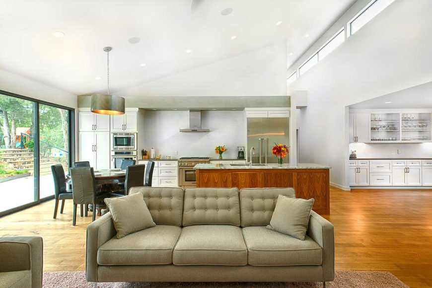 The contemporary sofas stand over a plush area rug, while the expanse of natural hardwood flooring spreads behind into a large kitchen area with circular dining table at left. Full height glass allows sunlight throughout the space.