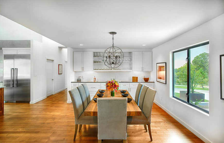 The immense dining room overlooks the front yard, with a lengthy hardwood dining table at center. White cabinetry for table settings matches those found in the kitchen at left.