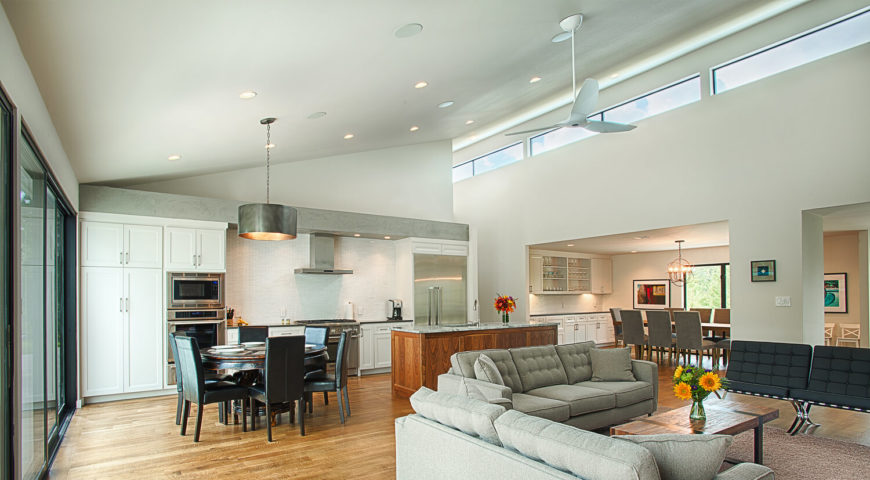 This wide view of the central space showcases the vast expanse of open air, connecting the disparate ends of the home. Rich wood, white walls, and muted grey and black tones keep the area grounded.
